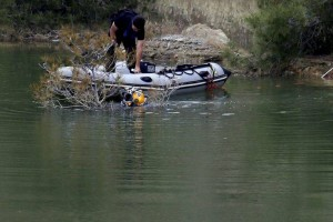 A diver in the water and an Investigator conduct a search near the village of Xiliatos,  Cyprus, Friday, April 26, 2019. Cyprus police are intensifying a search for the remains of more victims at locations where an army officer who authorities say admitted to killing five women and two girls had dumped their bodies. (AP Photo/Petros Karadjias)